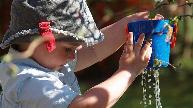 バケツの水漏れを見る子供