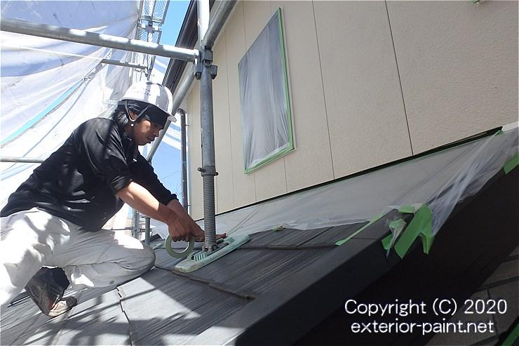 外壁塗装の養生をする職人