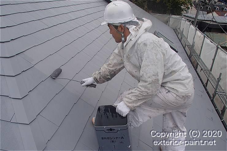 天辺を三角に切った持ち手の一斗缶で屋根を塗る職人