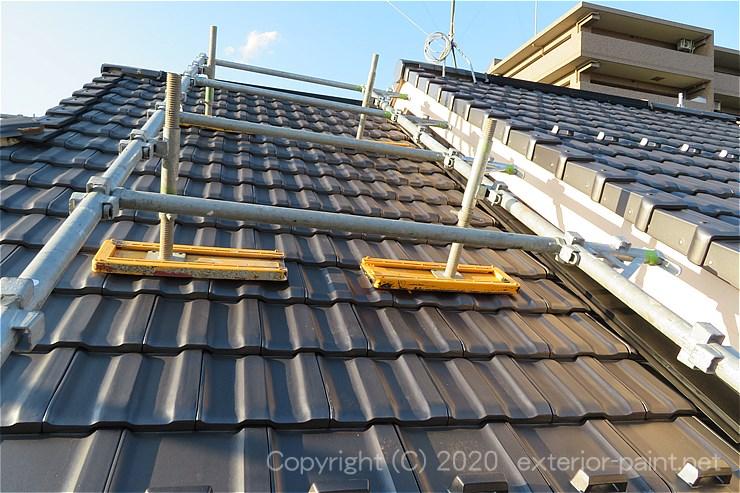 屋根の上にある破風板を塗装するための屋根足場